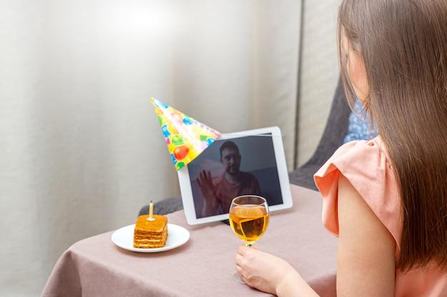 Młoda kobieta świętuje urodziny podczas kwarantanny. wirtualne przyjęcie urodzinowe online z przyjaciółką lub kochankiem. połączenie wideo na tablecie.