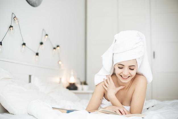 Młoda kobieta szczęśliwa czytanie papierowej książki w łóżku. kobieta z ręcznikiem na zagłówku w łóżku z książką.