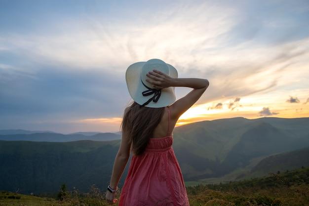 Młoda kobieta szczęśliwa podróżnik w czerwonej sukience stojący na trawiastym zboczu wzgórza w wietrzny wieczór w górach latem, ciesząc się widokiem natury o zachodzie słońca.
