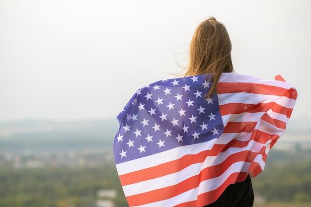 Młoda kobieta szczęśliwa z długimi włosami trzymając macha na wietrze amerykańską flagę narodową na jej sholders odpoczynku na świeżym powietrzu, ciesząc się ciepłym letnim dniem.