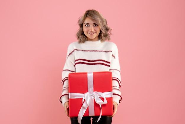 Młoda kobieta szczęśliwie trzymając świąteczny prezent na różowo