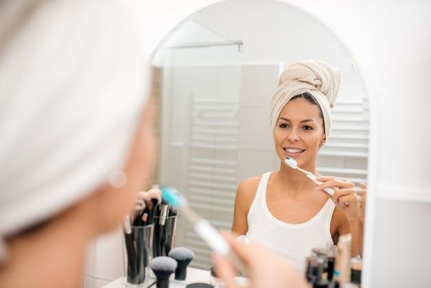 Młoda kobieta szczotkuje zęby po prysznic.