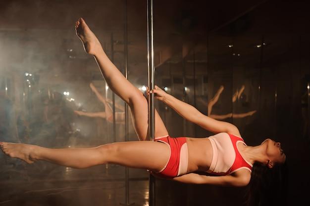 Młoda kobieta szczupła taniec na rurze rozciąganie w jasnym wnętrzu.