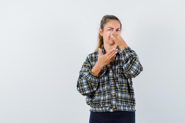Młoda kobieta szczypie nos z powodu nieprzyjemnego zapachu koszuli, szortów i wygląda na zniesmaczoną. przedni widok.