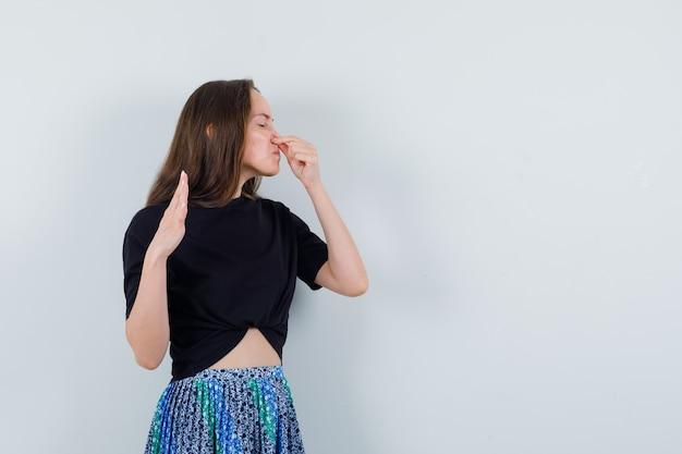 Młoda kobieta szczypie nos z powodu nieprzyjemnego zapachu w czarnej koszulce i niebieskiej spódnicy i wygląda na zirytowaną