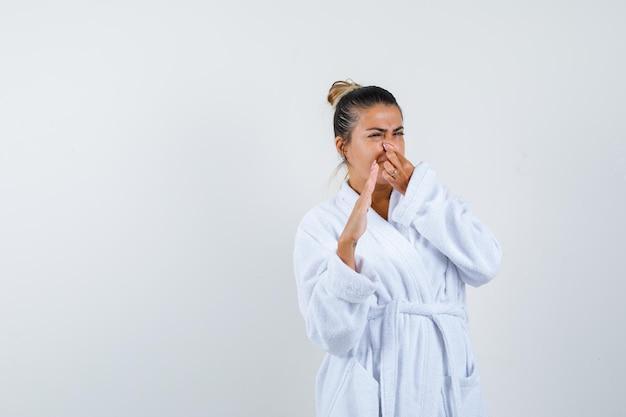 Młoda kobieta szczypie nos z powodu nieprzyjemnego zapachu w szlafroku i wygląda na zniesmaczoną