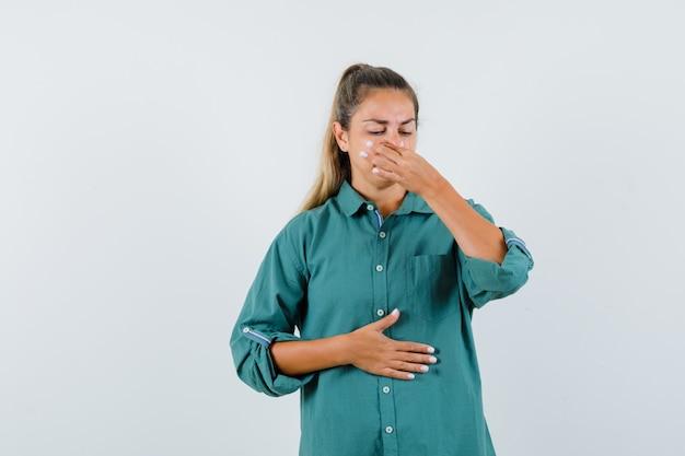 Młoda kobieta szczypie nos z powodu nieprzyjemnego zapachu w zielonej bluzce i wygląda na wyczerpaną