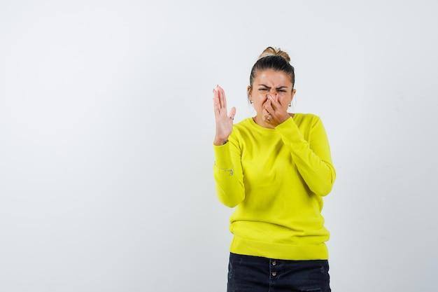 Młoda kobieta szczypie nos z powodu nieprzyjemnego zapachu w żółtym swetrze i czarnych spodniach i wygląda na zirytowaną