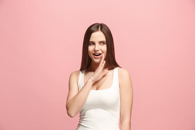 Młoda kobieta szepcząca sekret za dłonią na różowej ścianie