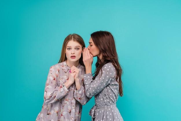 Młoda kobieta szepcze sekret swojej dziewczynie izolowanej na niebiesko