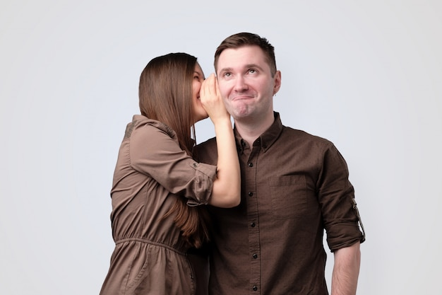 Młoda kobieta szepcze sekret swojemu chłopakowi