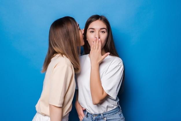 Młoda kobieta szepcze swojemu koledze złe wieści na białym tle na niebieskiej ścianie