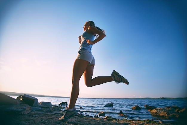 Młoda kobieta szkolenia na plaży