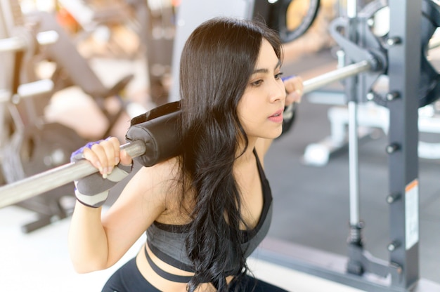 Młoda Kobieta Szkolenia Ze Sztangą Na Siłowni Premium Zdjęcia