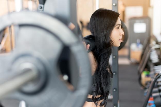 Młoda kobieta szkolenia ze sztangą na siłowni