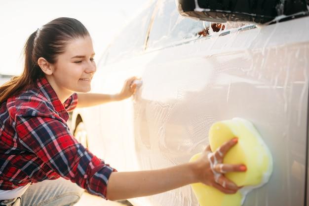 Młoda kobieta szorowania pojazdu z pianką