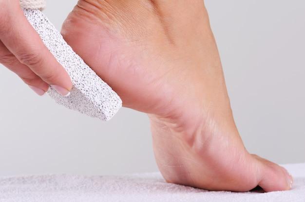Młoda kobieta szorując stopę pumeksem w salonie piękności