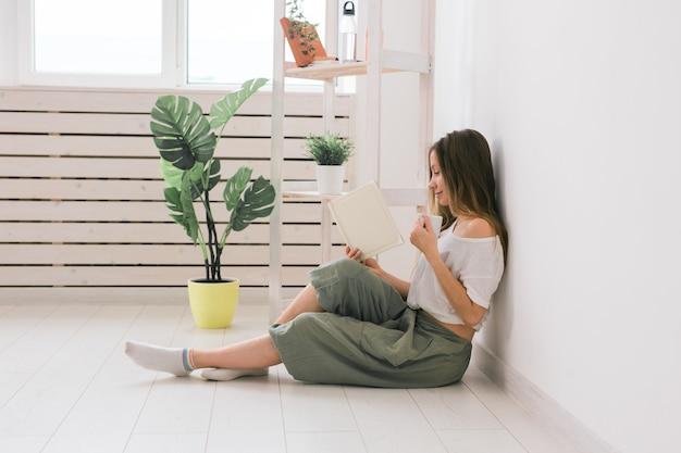 Młoda kobieta szuka albumu fotograficznego w domu i pije herbatę. wspomnienia i koncepcja wypoczynku.