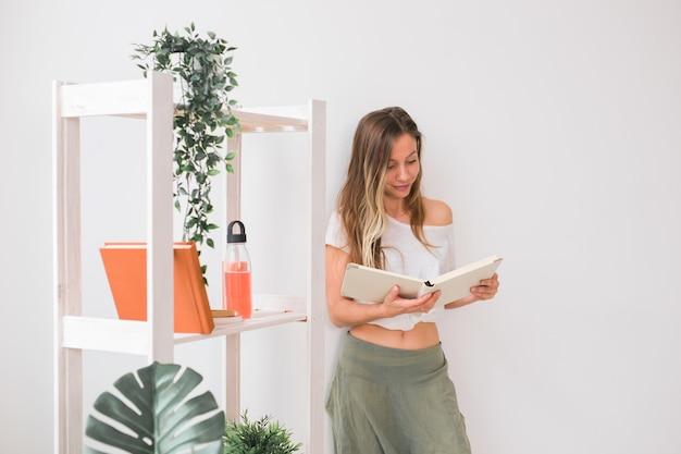 Młoda kobieta szuka albumu fotograficznego w domu, wspomnienia i koncepcja wypoczynku