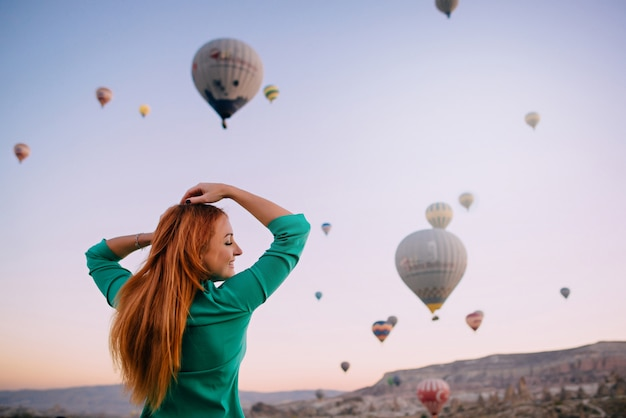 Młoda kobieta szuka balony rozpostartymi ramionami