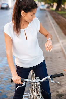 Młoda kobieta szuka czasu na jej zegarek, siedząc na rowerze