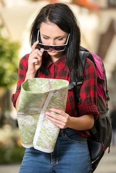 Młoda kobieta szuka miejsca na mapie w mieście.