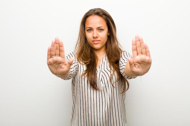 Młoda kobieta szuka poważnego, niezadowolonego, wściekłego i niezadowolonego zakazu wstępu lub mówi: przestań z otwartymi dłońmi na białej ścianie