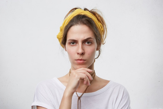 Młoda kobieta szuka sceptyka i trzymając rękę na brodzie.