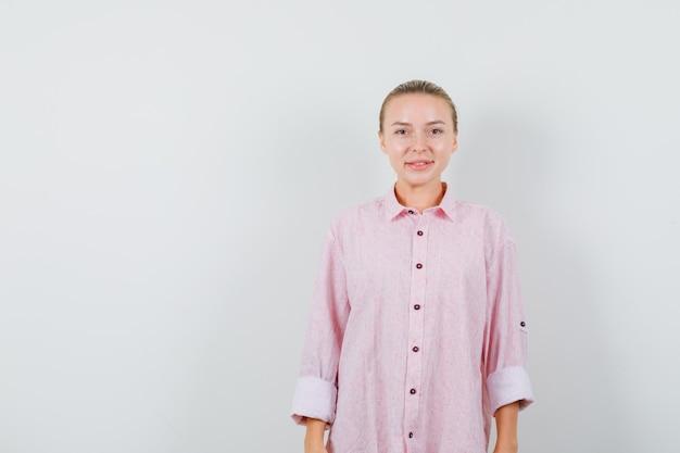 Młoda kobieta szuka w różowej koszuli i wygląda optymistycznie