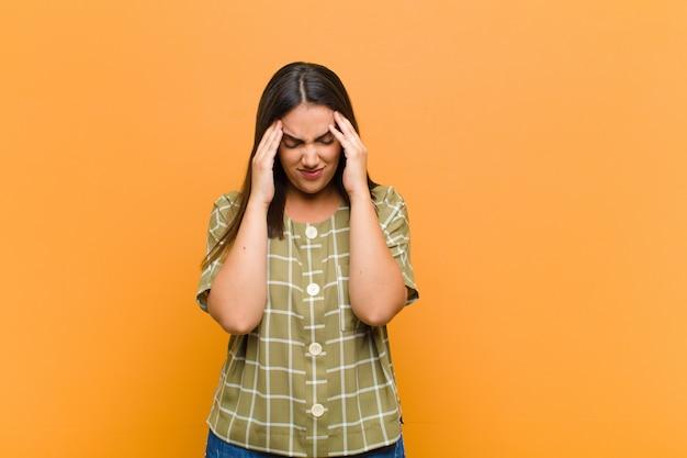 Młoda kobieta szuka zestresowany i sfrustrowany, pracując pod presją z bólem głowy i niepokojący się problemami na pomarańczowej ścianie