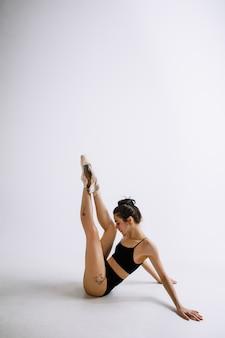 Młoda kobieta tancerka baletowa w czarnym body na ścianie białego studia