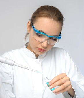 Młoda kobieta technika lub naukowiec ładuje płynną próbkę