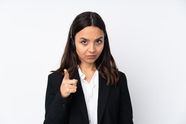Młoda kobieta telemarketer na białej ścianie sfrustrowany i wskazując na przód