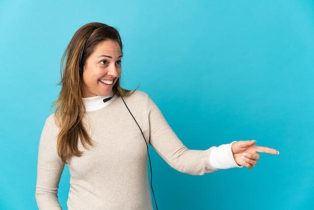 Młoda kobieta telemarketer na odosobnionej niebieskiej ścianie wskazując palcem z boku i prezentując produkt