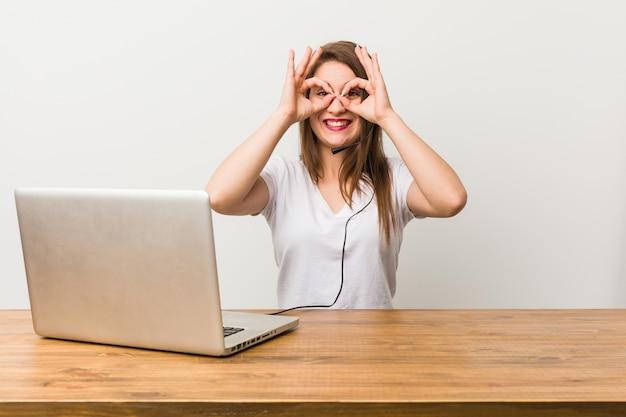 Młoda kobieta telemarketer pokazuje dobrze znak na oczach