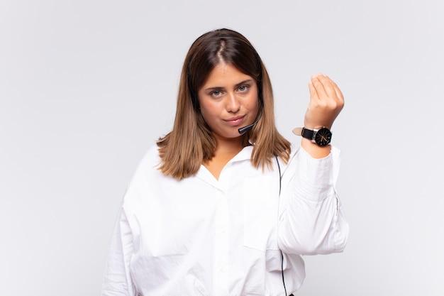 Młoda kobieta telemarketer robi gest kaprysu lub pieniędzy, każąc ci spłacić swoje długi!