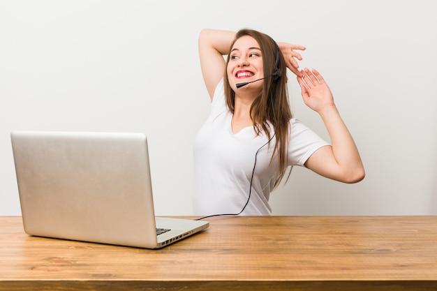 Młoda kobieta telemarketer, rozciąganie ramion, zrelaksowana pozycja.