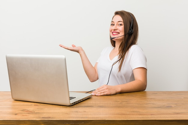 Młoda kobieta telemarketer trzyma kopię miejsca na dłoni.