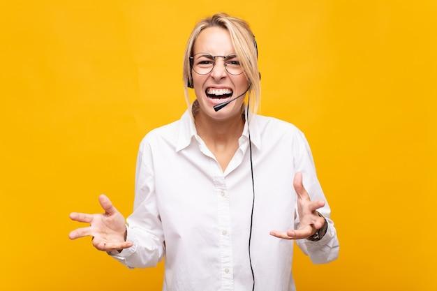 Młoda kobieta telemarketer wyglądająca na złą, zirytowaną i sfrustrowaną krzyczącą wtf lub co jest z tobą nie tak
