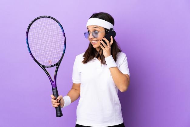 Młoda kobieta tenisista na białym tle prowadzenie rozmowy z telefonem komórkowym z kimś