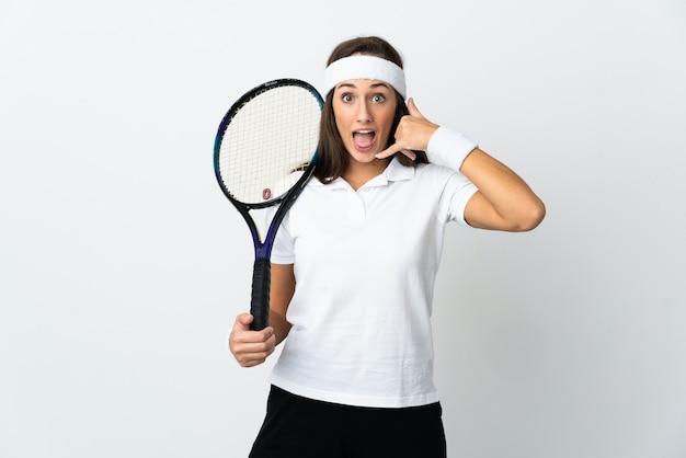 Młoda kobieta tenisista na na białym tle robi telefon gestowi. oddzwoń do mnie znak