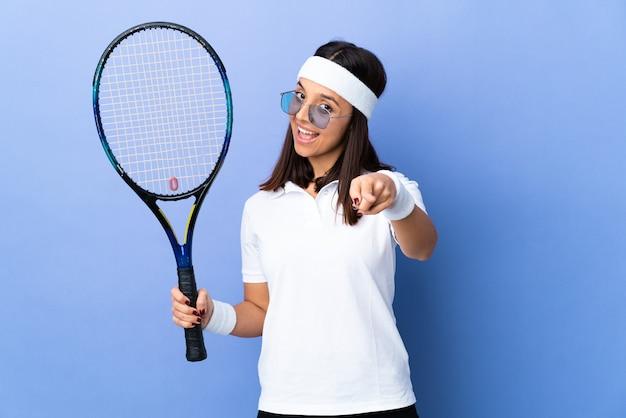 Młoda kobieta tenisista na odosobnionej ścianie robi telefon gest i wskazuje przód