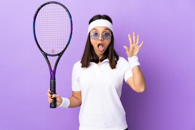 Młoda kobieta tenisista na pojedyncze ściany licząc pięć palcami