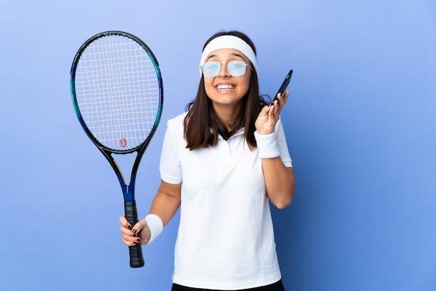 Młoda kobieta tenisista na ścianie prowadzenie rozmowy z telefonem komórkowym z kimś