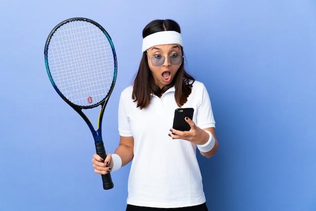 Młoda kobieta tenisista nad ścianą zaskoczony i wysyłanie wiadomości
