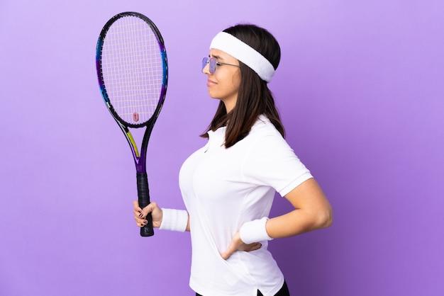 Młoda kobieta tenisistka nad ścianą cierpiącą na bóle pleców za dokonanie wysiłku
