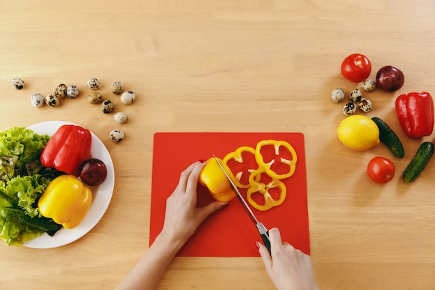 Młoda kobieta tnie żółtą paprykę na sałatkę nożem w kuchni. koncepcja diety. zdrowy tryb życia. gotowanie w domu. przygotuj jedzenie. widok z góry.