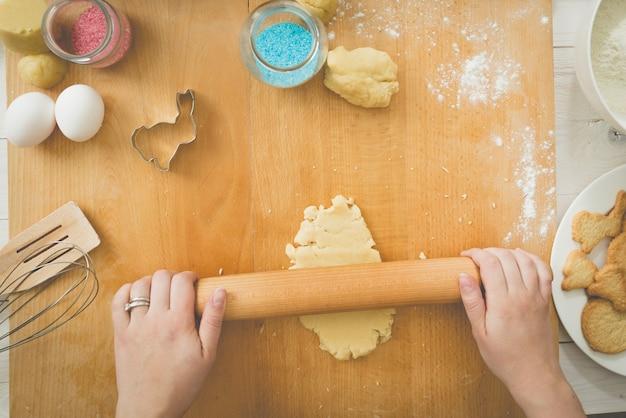 Młoda kobieta toczenia ciasta na drewnianej desce