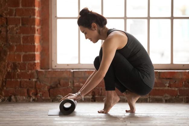 Młoda kobieta toczenia matą do ćwiczeń