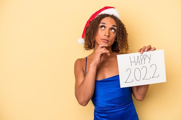 Młoda kobieta transseksualna łacińska świętuje nowy rok na białym tle na żółtym tle patrząc w bok z wyrazem wątpliwości i sceptyczny.